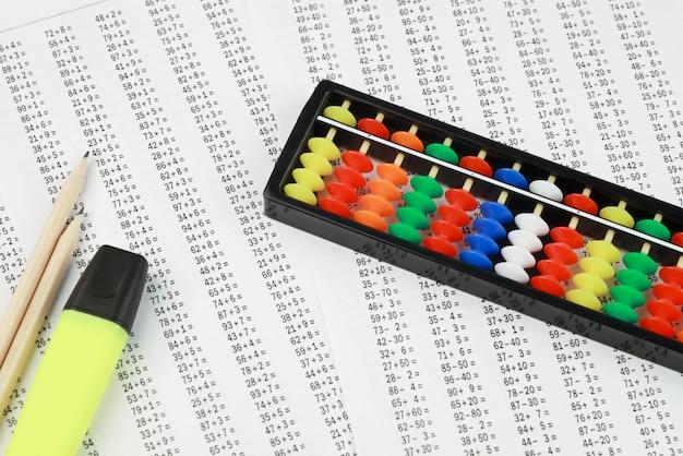 Abaco per l'aritmetica mentale, sullo sfondo di esempi da risolvere.