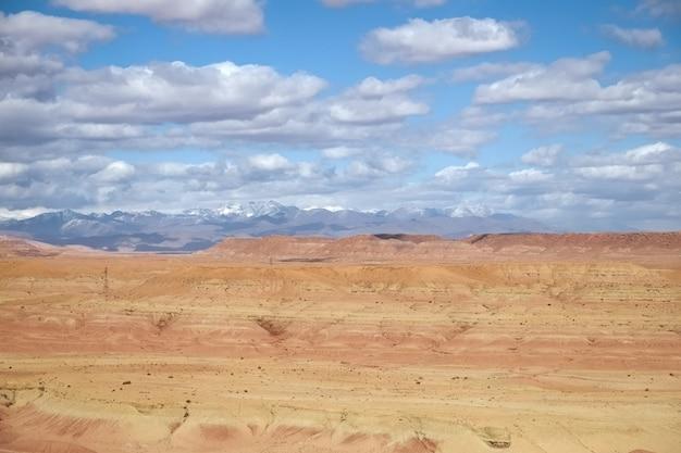 Abbandoni il paesaggio con un cielo blu nuvoloso e una catena montuosa ricoperta neve