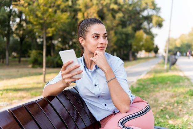 Abbastanza giovane che si siede su un banco con il telefono cellulare