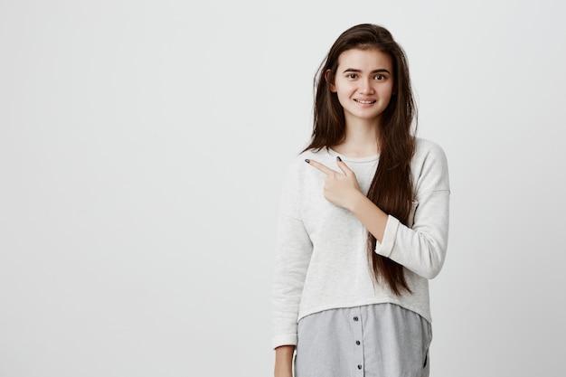 Abbastanza sorridente con gioia femmina con capelli lunghi scuri, indicando con il dito indice, mostrando lo spazio della copia