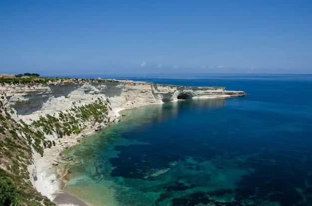 Abbellisca con il mar mediterraneo con acqua blu e le rocce bianche a malta vicino a marsaxlokk, stagno di st peter. percorso munxar