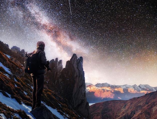 Abbellisca con la via lattea, le stelle del cielo notturno e la siluetta di un uomo diritto del fotografo sulla montagna.