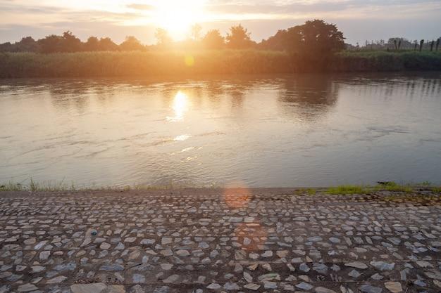 Abbellisca la riva del fiume di asiatico con la mattina del fiume del cannel