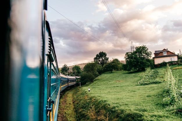 Abbellisca la vista dalla finestra dal treno di guida fra la natura dell'estate