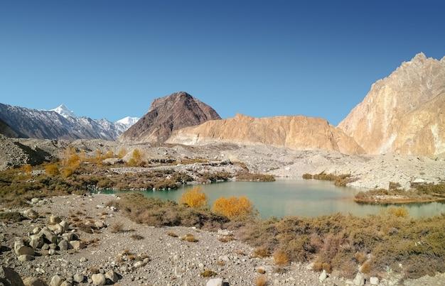 Abbellisca la vista del lago glaciale batura fra la catena montuosa di karakoram.
