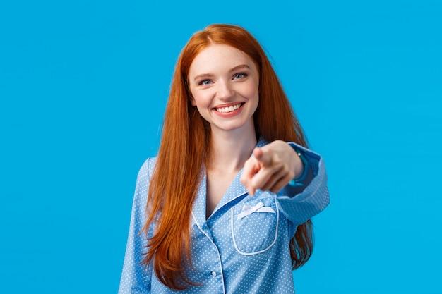 Abbiamo bisogno di voi. ragazza rossa allegra e fiduciosa facendo una scelta sicura, indicando il dito e sorridendo come decide, scegliendo tra le varianti, parlando con una persona, in piedi nella parete blu del pigiama
