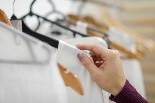 Abbigliamento bianco da donna sul gancio in negozio