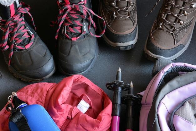 Abbigliamento da trekking per donna e uomo, composto da stivali, zaino, borraccia e bastoncini da passeggio