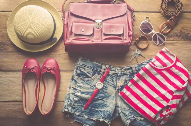 Abbigliamento e accessori per donna, posti su un pavimento di legno.