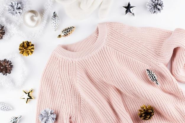 Abbigliamento invernale caldo e accogliente e decorazioni natalizie su bianco
