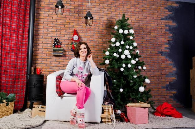 Abbigliamento ragazza su maglioni invernali in camera con decorazioni di natale.
