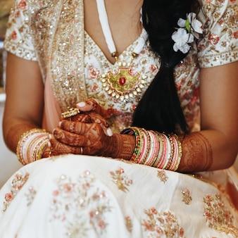Abbigliamento tradizionale indiano e braccialetti e le mani incrociate