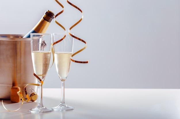 Abbina un bicchiere di champagne a una bottiglia in un contenitore di metallo. festa di capodanno