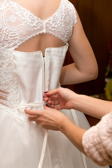 Abbottonarsi l'abito da sposa della sposa. avvicinamento.