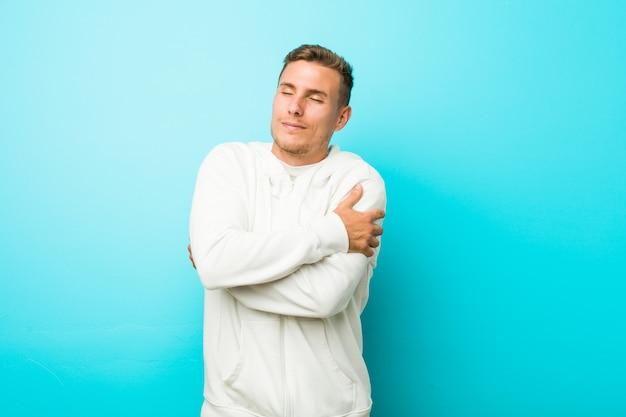 Abbracci caucasici del giovane uomo di sport, sorridenti spensierati e felici