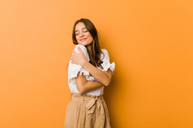 Abbracci caucasici della giovane donna, sorridenti spensierati e felici.