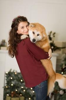 Abbracci di bella donna, coccole con il suo cane akita inu. su uno sfondo di un comò di albero di natale con candele in una stanza decorata. felice anno nuovo e buon natale