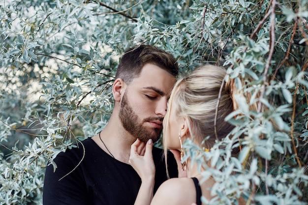 Abbracci e bacio amorevole coppia in rami di cespugli