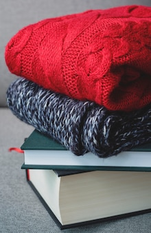 Abbracci il concetto dell'inverno di autunno, i maglioni rossi ed i libri su fondo grigio, il freddo, casa accogliente