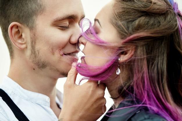 Abbraccia e bacia una coppia innamorata in una mattina di primavera nella natura. san valentino, uno stretto rapporto tra un uomo e una donna. uomo che bacia ragazza con capelli colorati luminosi, colorazione creativa
