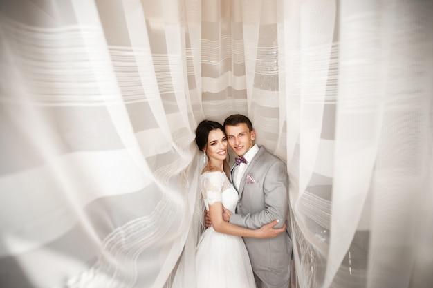 Abbraccia la giovane coppia il giorno del matrimonio