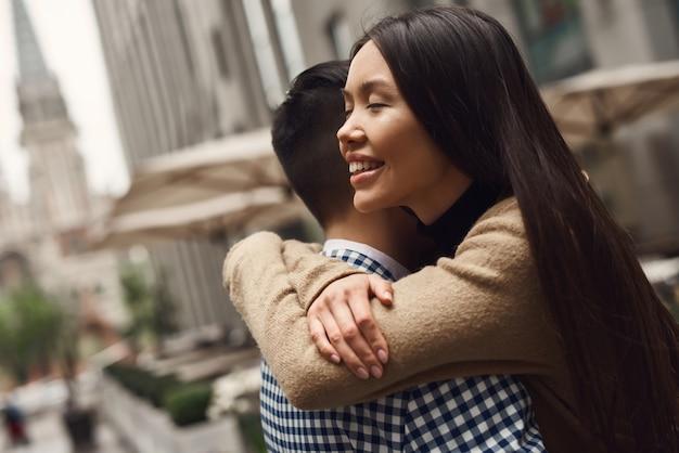 Abbracciando agli occhi chiusi di paesaggio urbano ragazza asiatica.
