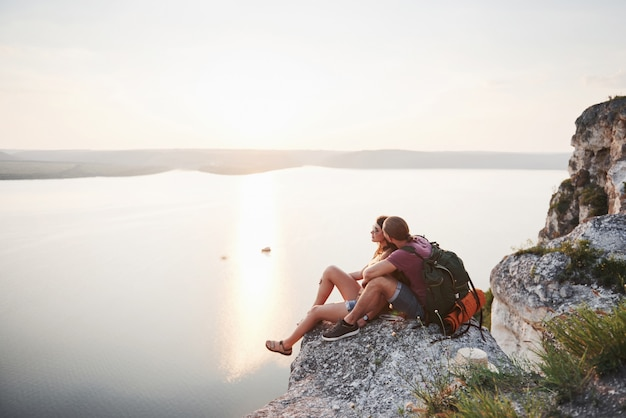 Abbracciando le coppie con lo zaino che si siede in cima alla montagna della roccia che gode della vista costeggia un fiume o un lago.