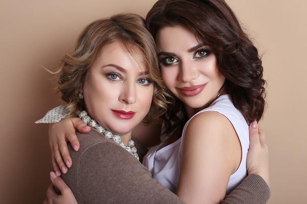 Abbracciare della figlia dell'adulto e della mamma, famiglia femminile