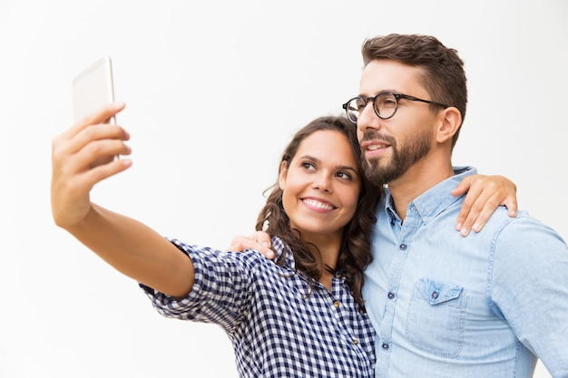 Abbracciare dolce allegro e prendere selfie sul cellulare