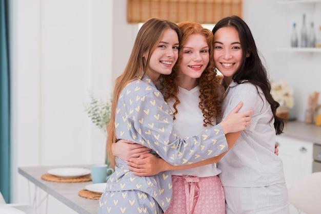 Abbracciare giovani amiche a casa