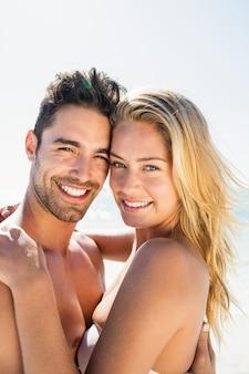 Abbracciare sorridente delle giovani coppie