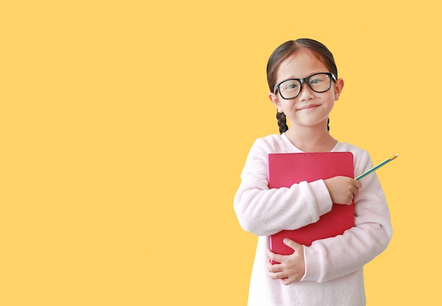 Abbraccio d'uso sorridente dell'occhiale della scolara un libro e giudicare matita a disposizione isolata sopra giallo.