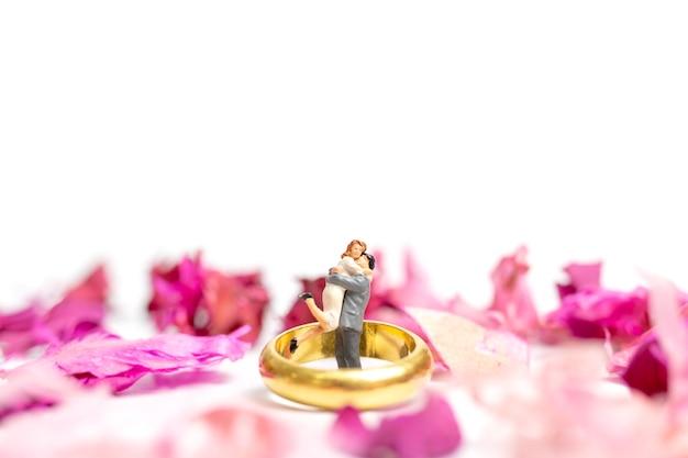 Abbraccio delle coppie nel giardino rosa con un anello di nozze