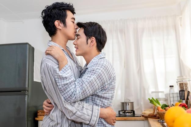 Abbraccio e bacio omosessuali asiatici delle coppie alla cucina di mattina. concetto lgbt gay.