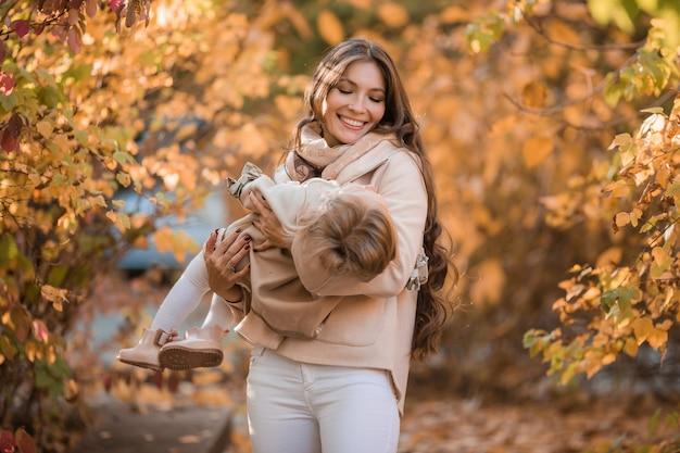 Abbraccio mamma e figlia nella foresta d'autunno