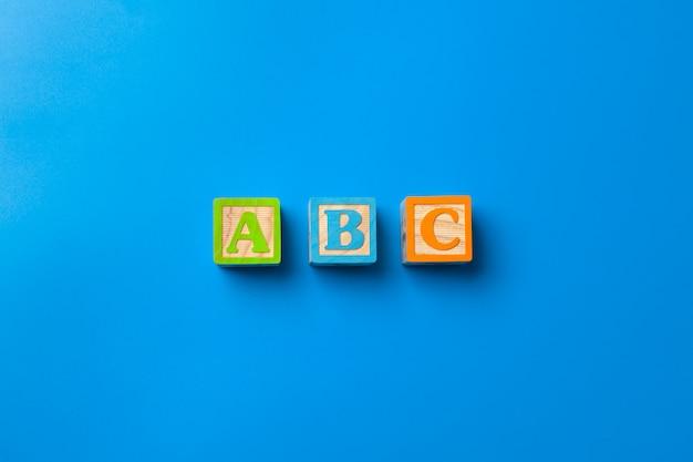 Abc. blocchetti di alfabeto variopinto di legno su fondo blu, disposizione piana, vista superiore.