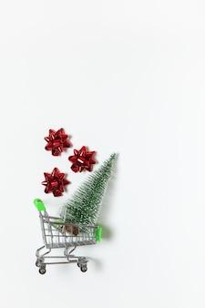 Abete di natale e fiocchi rossi per regalo nel carrello del giocattolo