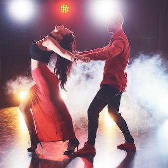 Abili ballerini si esibiscono nella stanza buia sotto la luce del concerto e il fumo. coppia sensuale che esegue una danza contemporanea artistica ed emotiva