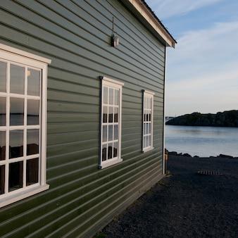 Abitazione colorata in riva al lago con tre finestre a più riquadri che disegnano la prospettiva verso l'orizzonte