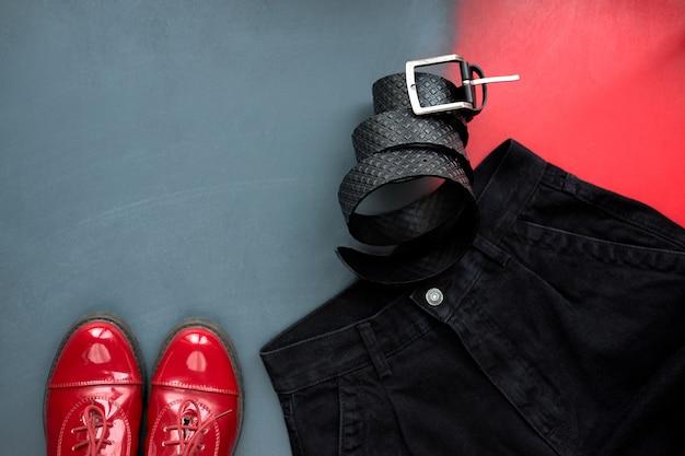 Abiti da donna alla moda. set di cintura in pelle nera alla moda, eleganti scarpe in vernice rossa e jeans neri su sfondo grigio e rosso. vista dall'alto.