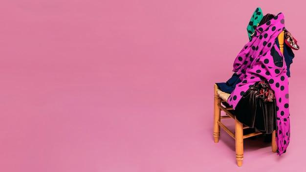 Abiti da flamenco su sedia con sfondo rosa