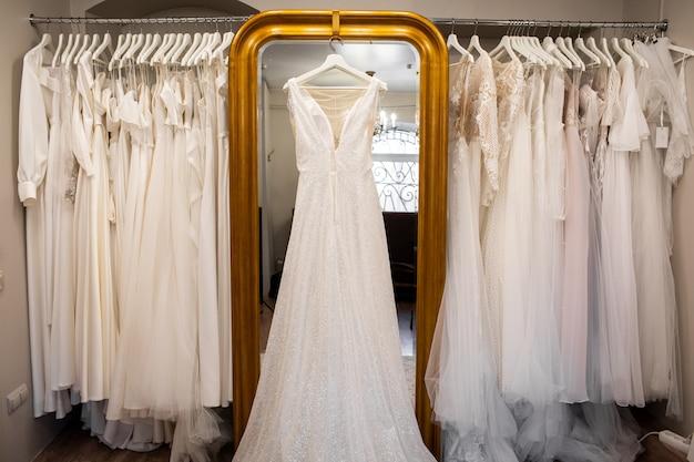 Abiti da sposa appesi su una gruccia. look alla moda. interno del salone nuziale.