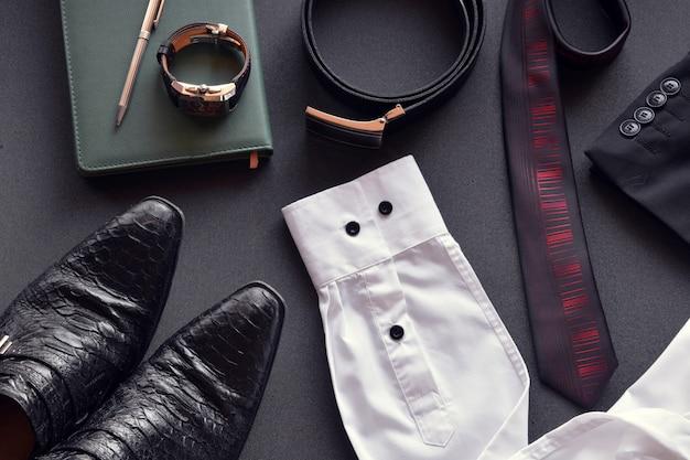 Abiti da uomo insieme a diversi accessori come orologio, calendario, cintura e scarpe