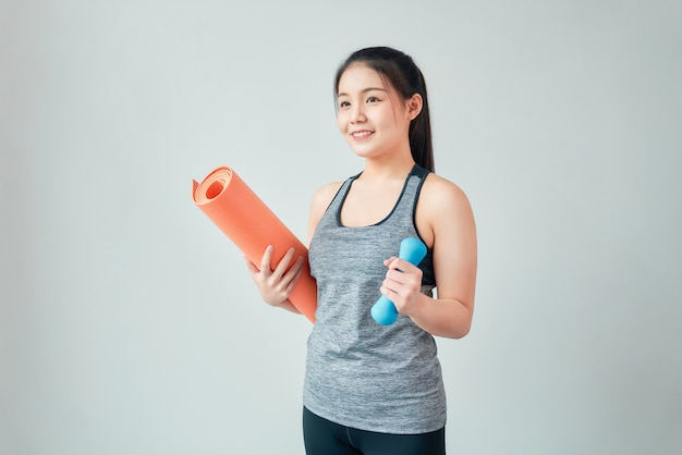 Abiti sportivi d'uso della donna asiatica di smiley che tengono stuoia arancio con la testa di legno blu in salone. concetto di stile di vita sano.