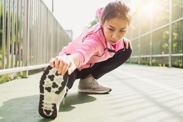 Abiti sportivi di moda ragazza sport fitness facendo esercizio di fitness yoga in strada