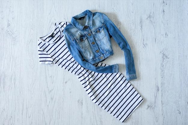 Abito a righe e giacca di jeans su fondo in legno. concetto alla moda