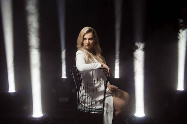 Abito bianco donna, modello fashion plus size in abito lungo bianco, ragazza in piedi con luci.