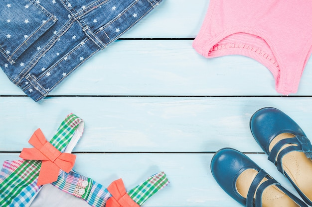 Abito colorato, scarpe, jeans e camicia rosa su fondo di legno pastello blu.
