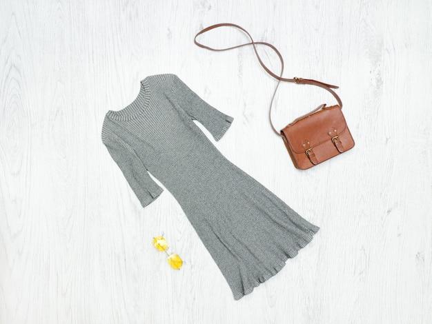 Abito corto grigio, borsa e occhiali da sole. concetto alla moda
