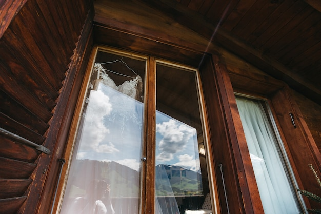Abito da sposa appeso a una finestra nell'enorme camera d'albergo in legno